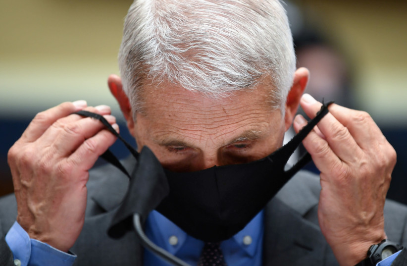 Director of the National Institute for Allergy and Infectious Diseases Dr. Anthony Fauci takes off his face mask prior testifying before the House Committee on Energy and Commerce on the Trump Administration's Response to the COVID-19 Pandemic, on Capitol Hill in Washington, DC, U.S. June 23, 2020 (photo credit: REUTERS)