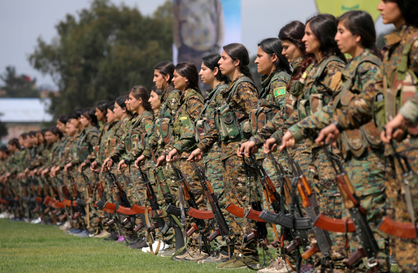 KURDISH FEMALE fighters of the Women's Protection Unit (YPJ) take part in a military parade as they celebrate victory over Islamic State, in Qamishli, Syria, in March 2019. (photo credit: REUTERS/RODI SAID)