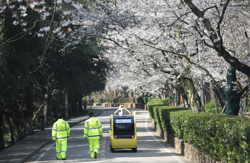 SECURITY PERSONNEL accompany a 5G-enabled autonomous vehicle, installed with a camera filming blooming cherry blossoms for an online live-streaming session, inside Wuhan University, Hubei province, China, on March 17. (photo credit: REUTERS)