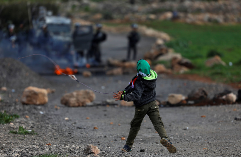 Palestinian boy hurls stones at Israeli troops during clashes in the West Bank (photo credit: REUTERS)