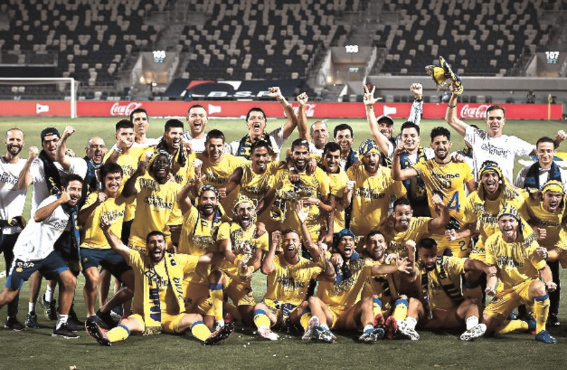 MACCABI TEL AVIV celebrates on the pitch at Bloomfield Stadium on Saturday night after beating Hapoel Tel Aviv 3-0 to clinch a second straight Premier League championship. (photo credit: ARIEL SHALOM)