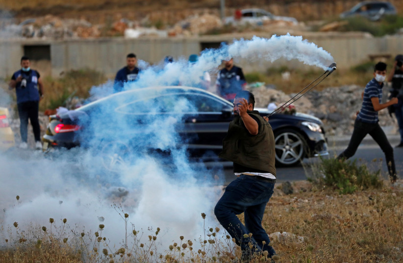 A Palestinian demonstrator returns a tear gas canister as a car carrying a bride and groom passes by during a protest against Israel's plan to annex parts of the West Bank, near the Beit El settlement. July 1, 2020. (photo credit: REUTERS/MOHAMAD TOROKMAN)