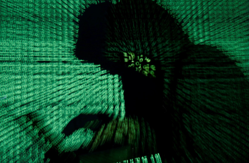 [Illustrative] A man holds a laptop computer as cyber code is projected on him. (photo credit: KACPER PEMPEL/REUTERS)