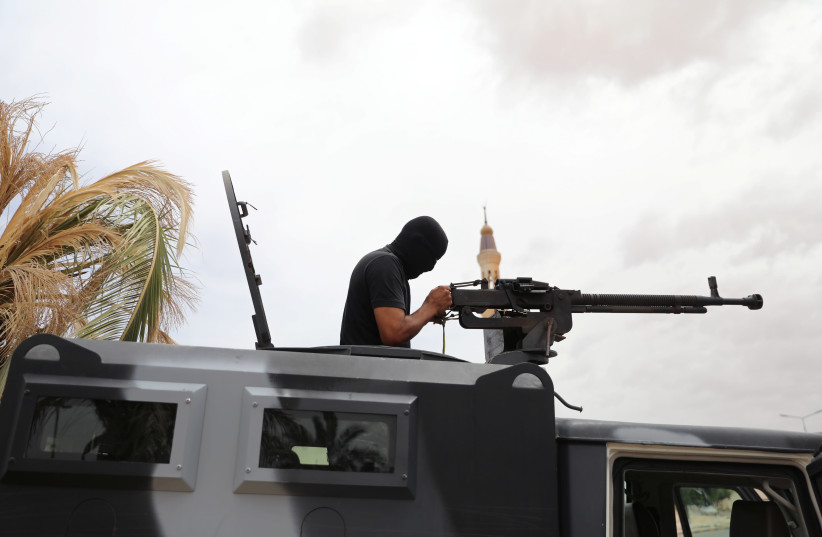 A member of security forces loyal to Libya's internationally recognised government checks his weapon during a security deployment in Tarhouna city, Libya June 11, 2020.  (photo credit: ISMAIL ZITOUNY/ REUTERS)