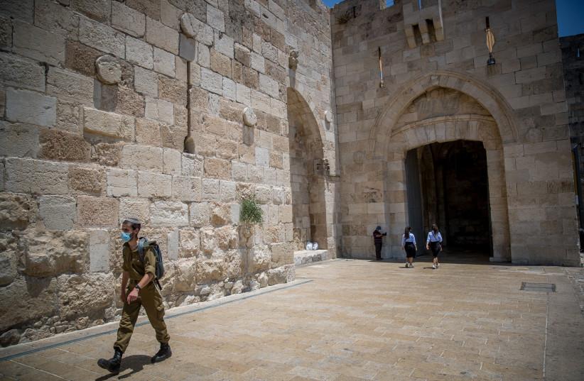 An Israeli soldier wearing a face mask walking in Jaffa Gate, outside Jerusalem Old City on July 5, 2020. (photo credit: YONATAN SINDEL/FLASH90)