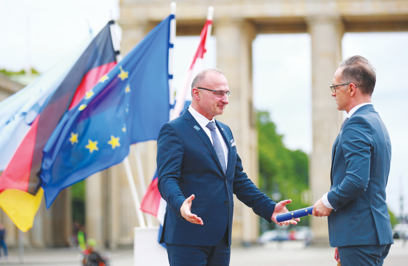 GERMAN FOREIGN Minister Heiko Maas (right) takes over the rotating presidency of the Council of the European Union from Croatian Foreign Minister Gordan Grlic-Radman during a symbolic handover in front of the Brandenburg Gate in Berlin last week. (photo credit: HANNIBAL HANSCHKE/REUTERS)