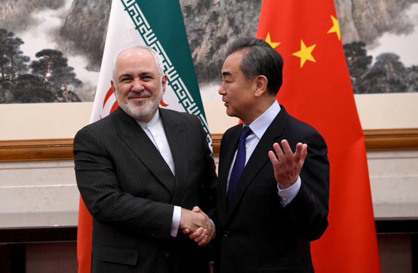 China's Foreign Minister Wang Yi shakes hands with Iran's Foreign Minister Mohammad Javad Zarif during a meeting at the Diaoyutai state guest house in Beijing, China December 31, 2019. (photo credit: REUTERS)