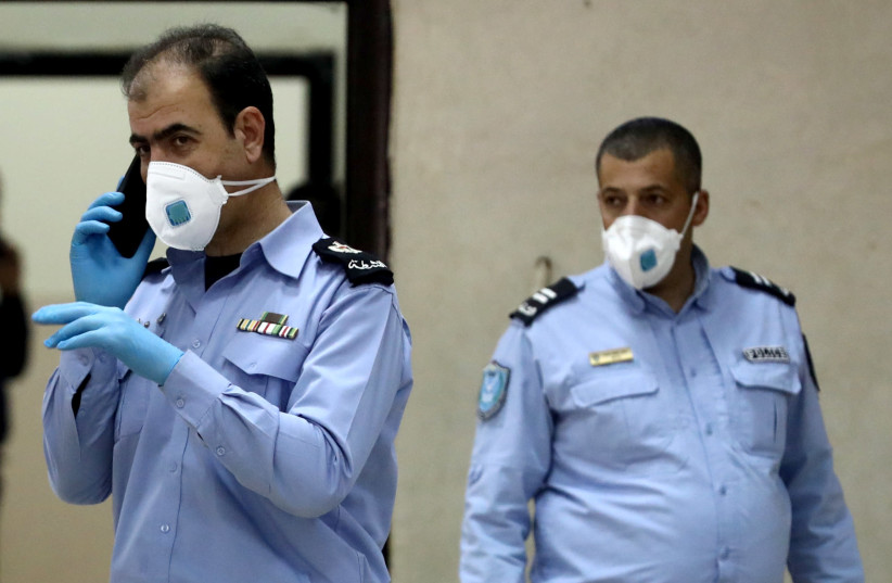 Palestinian police officers, wearing masks as a preventive measure against coronavirus (photo credit: REUTERS/AMMAR AWAD)