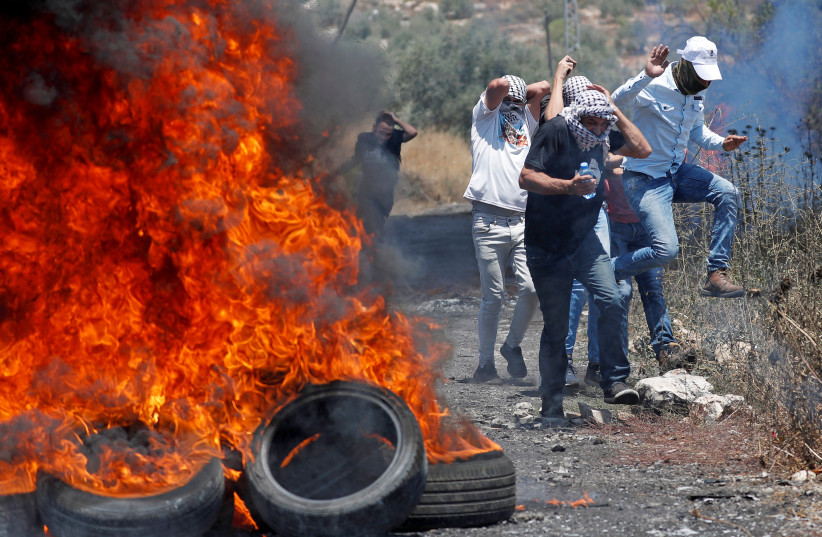 Palestinian demonstrators react to Israeli gunfire during a protest against Israel's plan to annex parts of the West Bank, in Kafr Qaddum near Nablus July 3, 2020. (photo credit: MOHAMAD TOROKMAN/REUTERS)