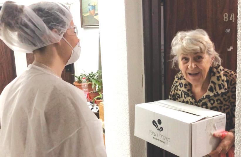 A Leket Israel volunteer delivers food to a housebound woman. (photo credit: COURTESY LEKET ISRAEL)