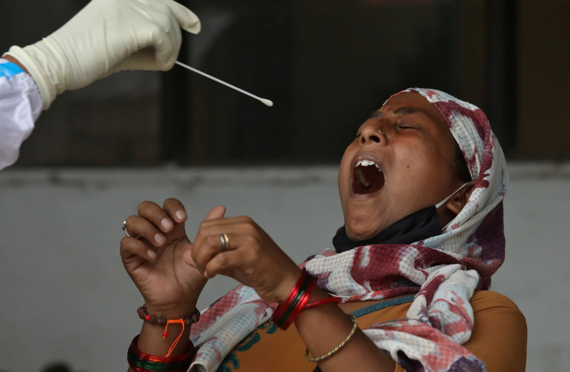 A woman reacts as a healthcare worker takes a swab from her to test for the coronavirus disease (COVID-19) in Kolkata, India July 10, 2020. (photo credit: REUTERS)