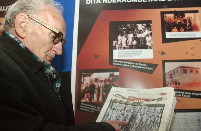 Beqir Xhepa, 80, an Albanian who was caught as a partisan courier by the Germans during World War Two and sent to the concentration camps at Mathausen and Auschwitz, points at himself in a picture taken when he was a prisoner, in Tirana, January 27, 2005 (photo credit: REUTERS)