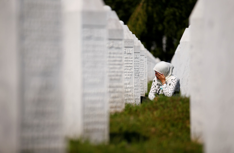 A woman cries at a graveyard, ahead of a mass funeral in Potocari near Srebrenica, Bosnia and Herzegovina July 11, 2020. Bosnia marks the 25th anniversary of the massacre of more than 8,000 Bosnian Muslim men and boys, with many relatives unable to attend due to the coronavirus disease (COVID-19) ou (photo credit: REUTERS/DADO RUVIC)