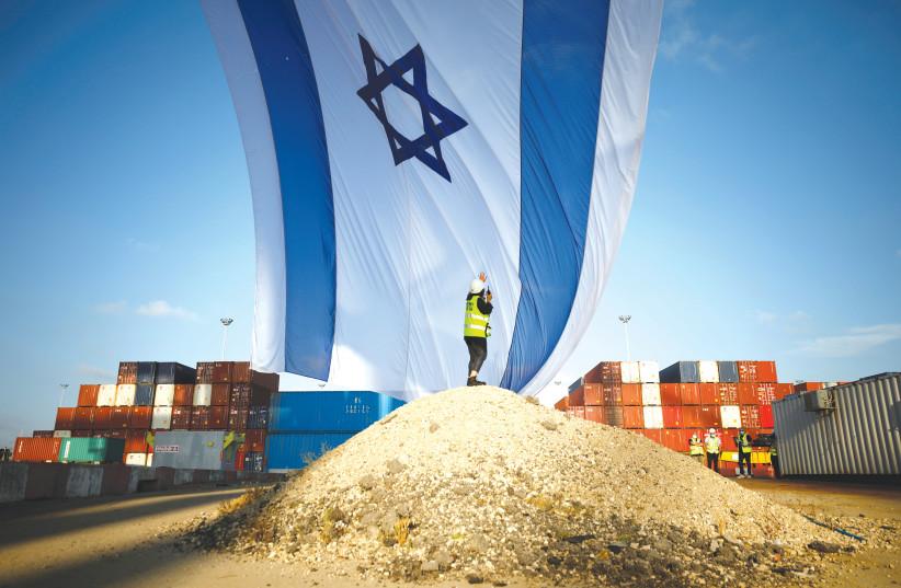 A WORKER at Ashdod port coordinates a crane to hang a giant Israeli national flag. (photo credit: REUTERS/AMIR COHEN)