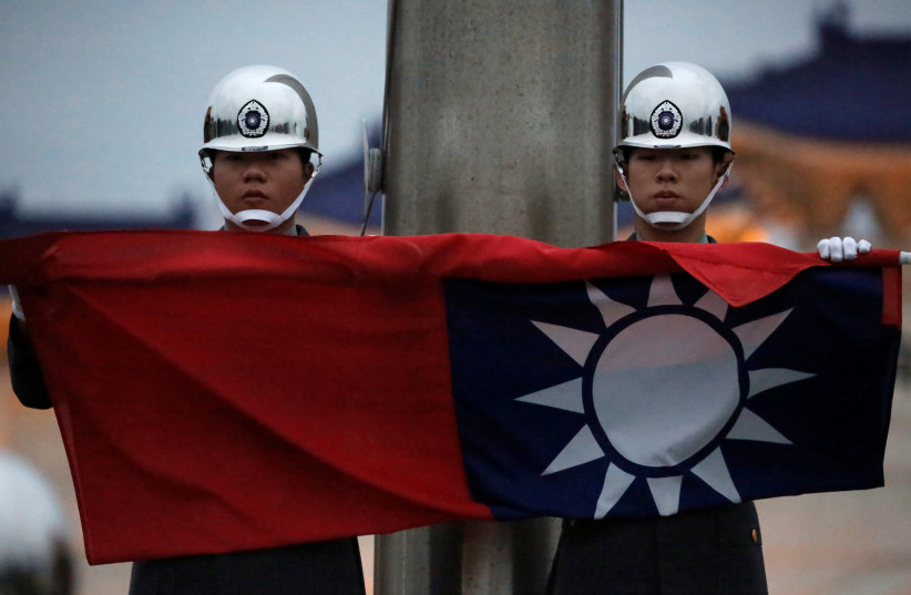 Honor guards perform Taiwan national flag lowering ceremony at Liberty Square in Taipei, as the spread of the coronavirus disease (COVID-19) continues, in Taipei, Taiwan, April 1, 2020. (photo credit: REUTERS)