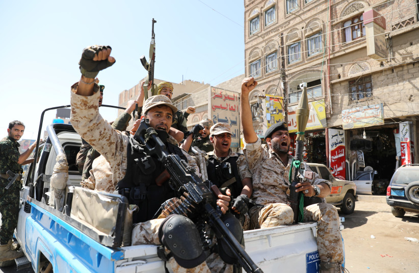 Houthi troops ride on the back of a police patrol truck after participating in a Houthi gathering in Sanaa, Yemen (photo credit: KHALED ABDULLAH/ REUTERS)