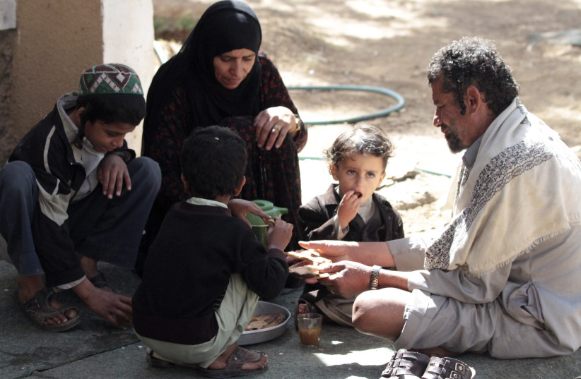 A family have breakfast outside their home at a Jewish community in Sanaa, Yemen (photo credit: MOHAMED AL-SAYAGHI/REUTERS)