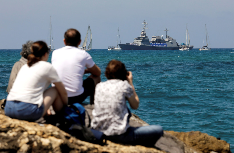 People watch an Israeli Navy corvette vessel, in the Mediterranean Sea during a marine show as part of the celebrations for Israel's Independence Day marking the 70th anniversary of the creation of the state, in Tel Aviv, Israel April 19, 2018 (photo credit: REUTERS/AMIR COHEN)