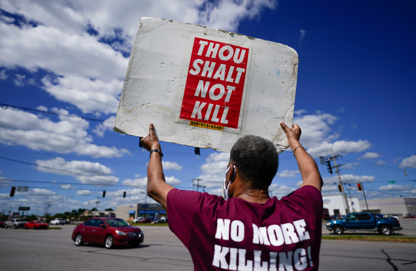 Reverend Sylvester Edwards, President of the Terre Haute NAACP, stands near the Federal Correctional Institution, Terre Haute, to express his opposition to the death penalty and execution of Daniel Lewis Lee. July 13, 2020 (photo credit: BRYAN WOOLSTON/REUTERS)