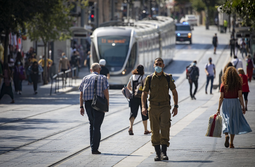 Jerusalemites wearing face masks for fear of coronavirus  walk on Jaffa road in the City Center of Jerusalem on July 12, 2020. Israel has seen a spike of new COVID-19 cases,  cabinet ministers imposed new restrictions on public gatherings in a bid to stem the rising infection rate of the coronavirus (photo credit: OLIVIER FITOUSSI/FLASH90)