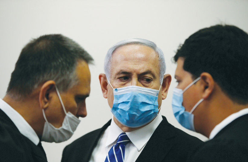 PRIME MINISTER Benjamin Netanyahu with members of his legal team at the beginning of his corruption trial at the Jerusalem District Court in May. (photo credit: RONEN ZVULUN/REUTERS)