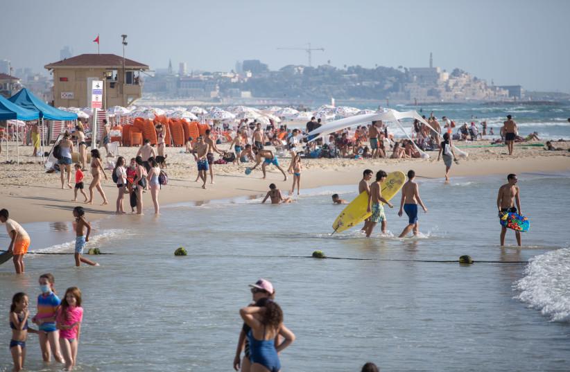 Israelis enjoy the beach in Tel Aviv, July 15, 2020 (photo credit: MIRIAM ALSTER/FLASH90)