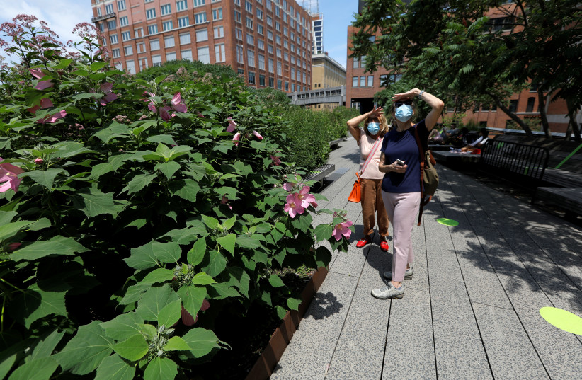 Women wearing protective face masks pause to take in a view as they walk on the elevated High Line Park in Manhattan on the first day of the park's re-opening following the outbreak of the coronavirus disease (COVID-19) in New York City, New York, U.S., July 16, 2020 (photo credit: REUTERS/MIKE SEGAR)