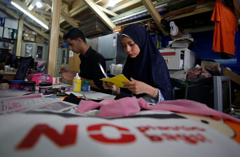 Palestinians decorate cloth bags as part of a project aiming at replacing plastic bags in shops, in Gaza City July 12, 2020 (photo credit: REUTERS/MOHAMMED SALEM)