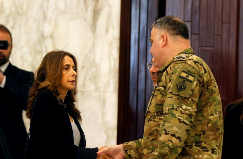 Lebanese Deputy Prime Minister and Defense Minister Zeina Akar shakes hands with a military personnel as she arrives to attend the cabinet meeting at the presidential palace in Baabda (photo credit: REUTERS/MOHAMED AZAKIR)