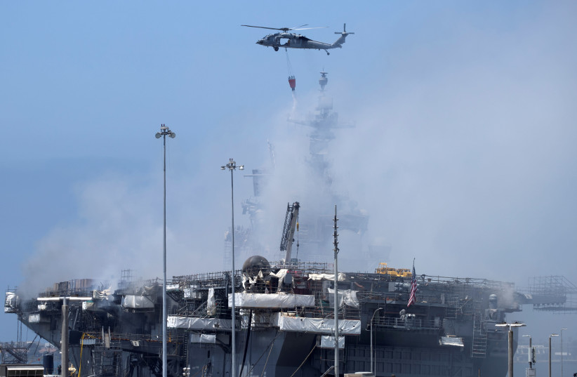 A US Navy helicopter continues fighting a fire on the amphibious assault ship USS Bonhomme Richard at Naval Base San Diego, in San Diego, California, US July 13, 2020 (photo credit: REUTERS/MIKE BLAKE)