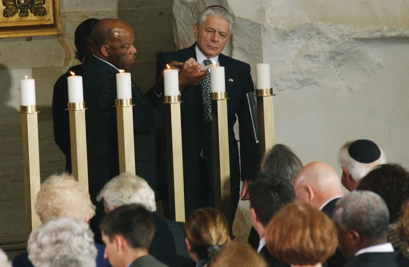 John Lewis, D-Ga., and Norbert Bikales, who was part of the Kindertransport from Berlin to France in July 1939 following the deportation of his parents and brother to Poland, light one of six candles representing the more than six million Jews who were killed during the Holocaust, in a ceremony in t (photo credit: SCOTT J. FERRELL/CONGRESSIONAL QUARTERLY/GETTY IMAGES)