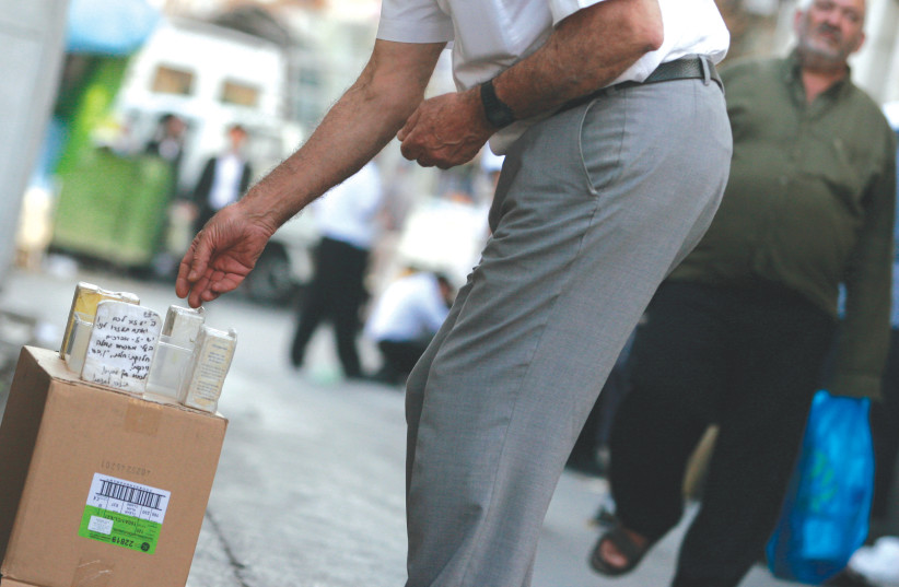 A man puts money into a charity box, in the streets of Mea She'arim in Jerusalem.  (photo credit: KOBI GIDEON/FLASH90)