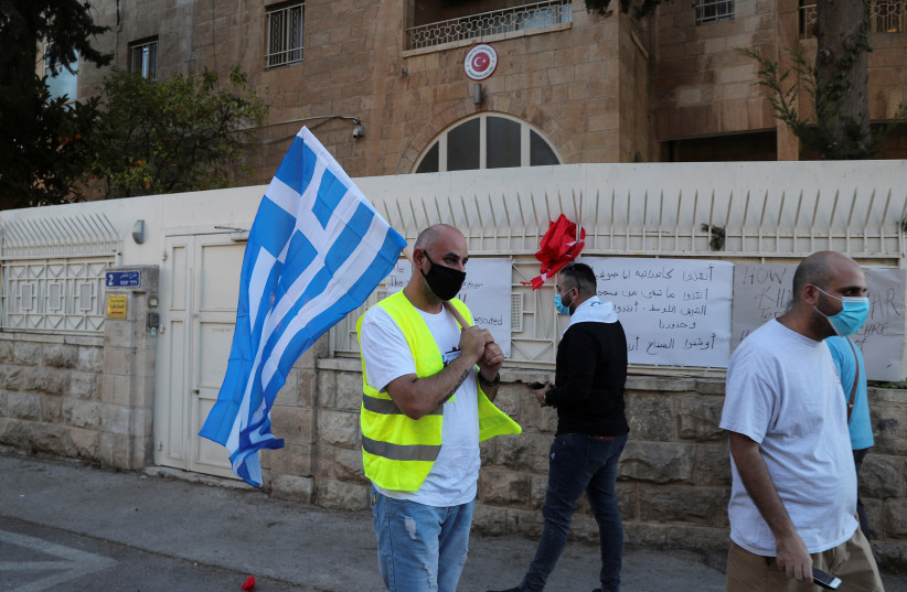 A Palestinian Christian man carries a Greek flag outside Turkey's consulate, during a protest against Ankara's decision to convert Istanbul's ancient Hagia Sophia from a museum back into a mosque, in Jerusalem July 13, 2020. (photo credit: REUTERS/AMMAR AWAD)