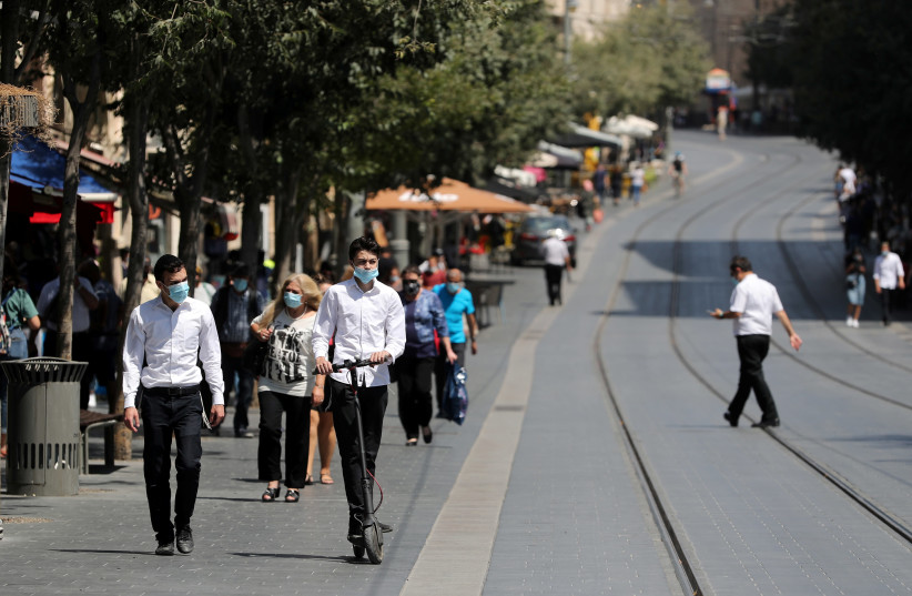 People wear protective masks as they walk around central Jerusalem amid the spread of the coronavirus disease (COVID-19), July 7, 2020 (photo credit: REUTERS/AMMAR AWAD)