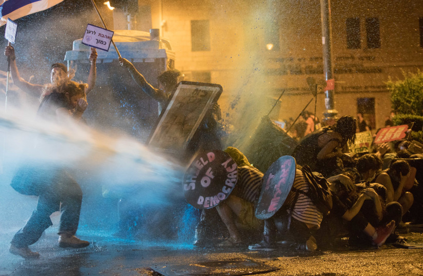 Israeli Police use a water cannon to disperse demonstrators during a protest against Prime Minister Benjamin Netanyahu outside the Prime Minister's Residence, Jerusalem, July 25, 2020 (photo credit: NOAM REVKIN FENTON/FLASH90)