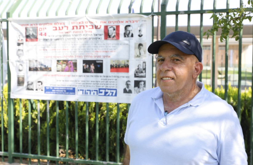 Elie Joseph in front of his banner protesting Israeli arms sales to major human rights violators, Jerusalem, July 2020 (photo credit: MARC ISRAEL SELLEM/THE JERUSALEM POST)
