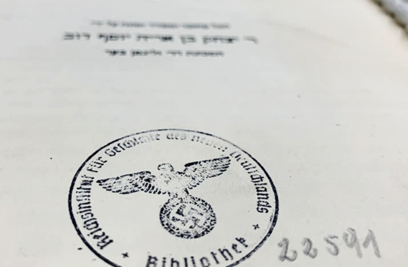 """A stamp featuring a Nazi """"Imperial Eagle"""" clutching a swastika - the """"Reichsadler"""", found on the siddur's title page (photo credit: UDI EDERY)"""
