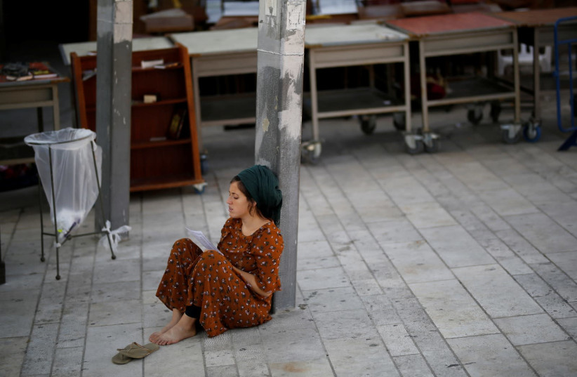 A Jewish worshipper prays next to the Western Wall on Tisha B'Av, a day of fasting and lament, in Jerusalem's Old City (photo credit: REUTERS/AMIR COHEN)