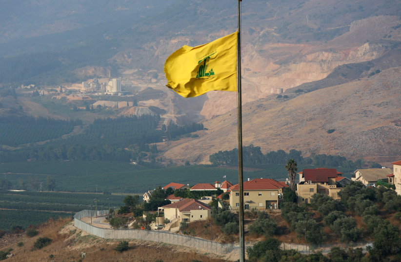 A Hezbollah flag flutters in the southern Lebanese village of Khiam, near the border with Israel, Lebanon July 28, 2020 (photo credit: REUTERS/AZIZ TAHER)