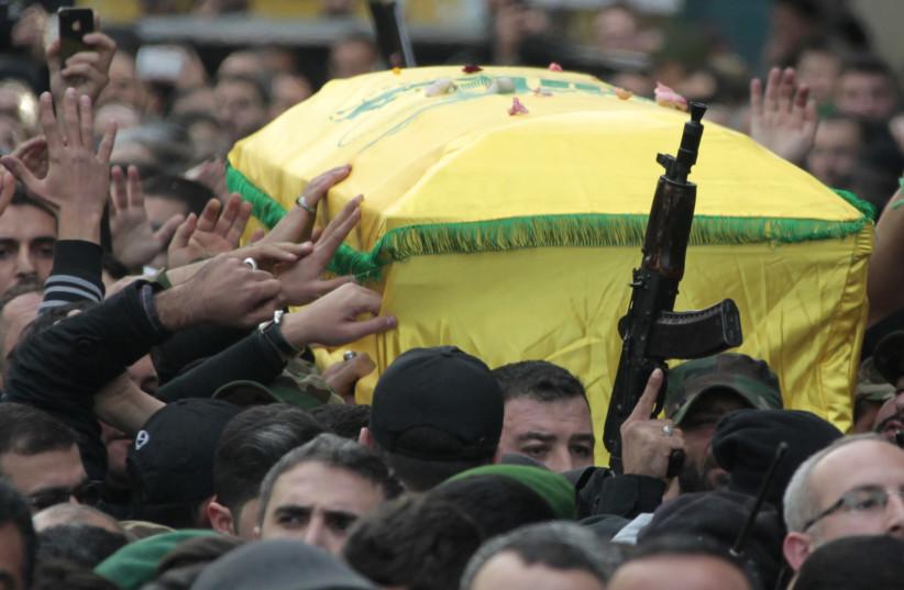 Les membres du Hezbollah libanais lèvent les poings et les fusils tout en portant le cercueil de Jihad Moughniyah lors de ses funérailles dans la banlieue de Beyrouth, 2015 (crédit photo: AZIZ TAHER / REUTERS)