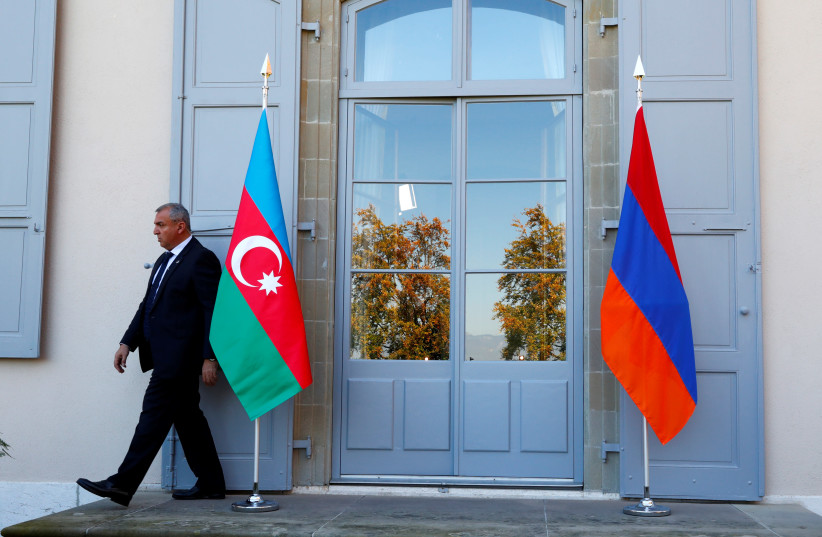 A security guard walks past an Azeri (L) and Armenian flag at the opening of talks in Geneva, Switzerland, October 16, 2017. (photo credit: REUTERS/DENIS BALIBOUSE)