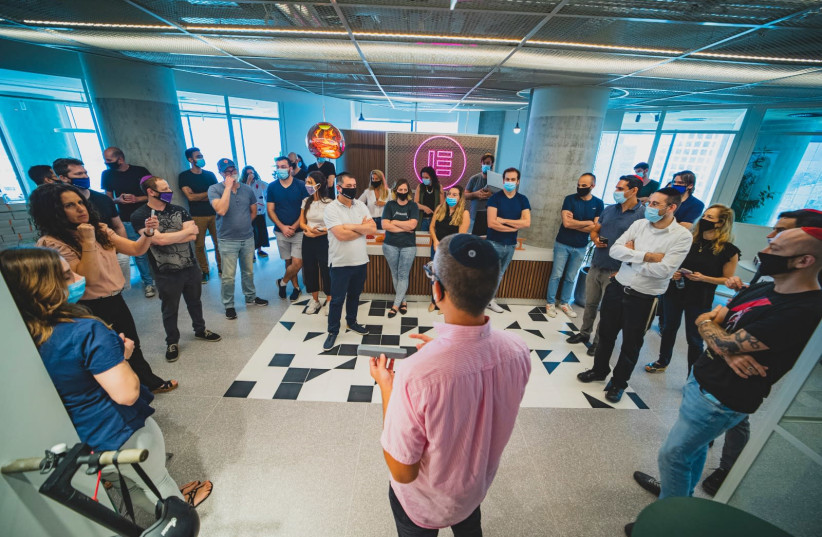 """Elementor workers with masks stand in their new hybrid office space.  """"A work space is like an anchor,"""" co-founder Yoni Luksenberg told the Post, """"this is the office of the post-coronavirus age."""" (photo credit: Courtesy)"""