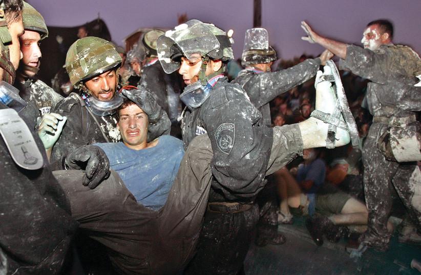 LES FORCES DE SÉCURITÉ ISRAÉLIENNES évacuent un opposant au plan de désengagement de Kfar Darom dans le bloc d'implantation du Gush Katif en août 2015. (Crédit photo: NIR ELIAS / REUTERS)