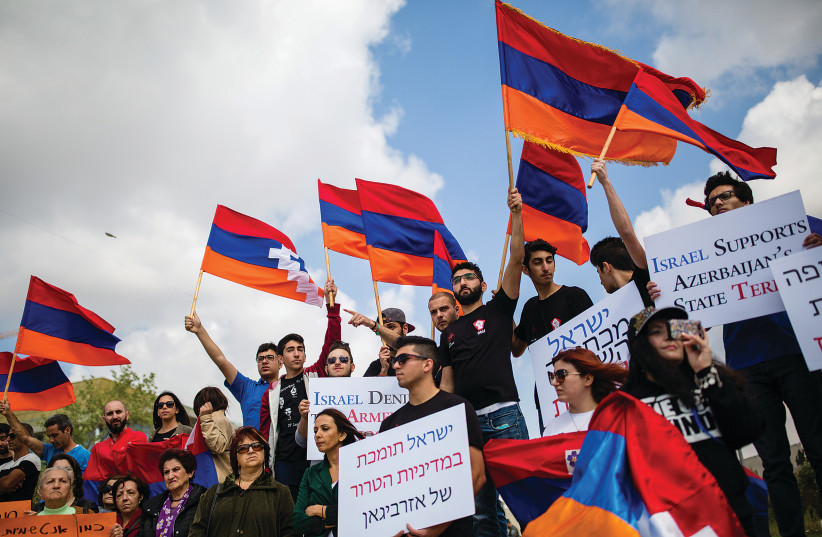 MEMBERS OF THE Armenian community of Jerusalem hold signs and Armenian flags as they protest in front of the Foreign Ministry against Israel's weapon sales to Azerbaijan in 2016. (photo credit: CORINNA KERN/FLASH90)