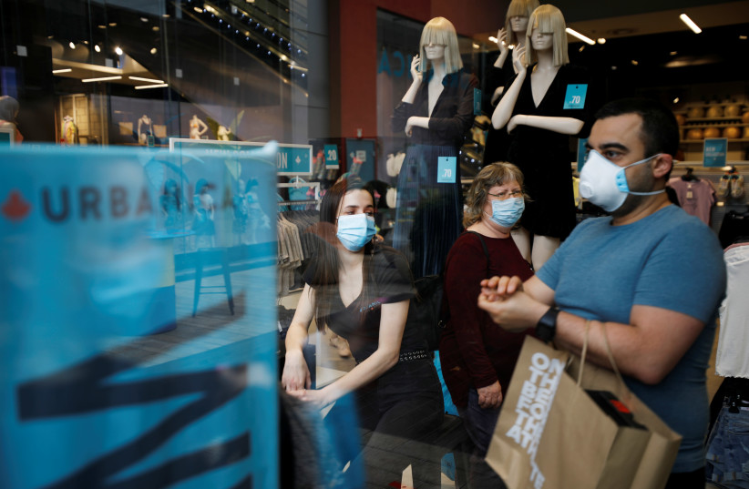 Shoppers wear face masks and walk around a fashion shopping center in Ashdod, as restrictions over the coronavirus disease (COVID-19) ease around Israel, May 5, 2020 (photo credit: REUTERS/AMIR COHEN)