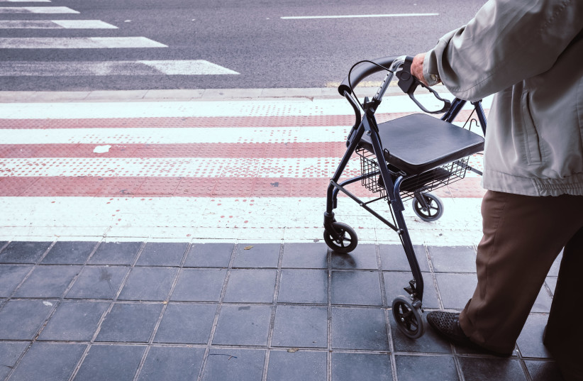Elderly man alone disabled, using a walker to help him walk. (photo credit: ING IMAGE)