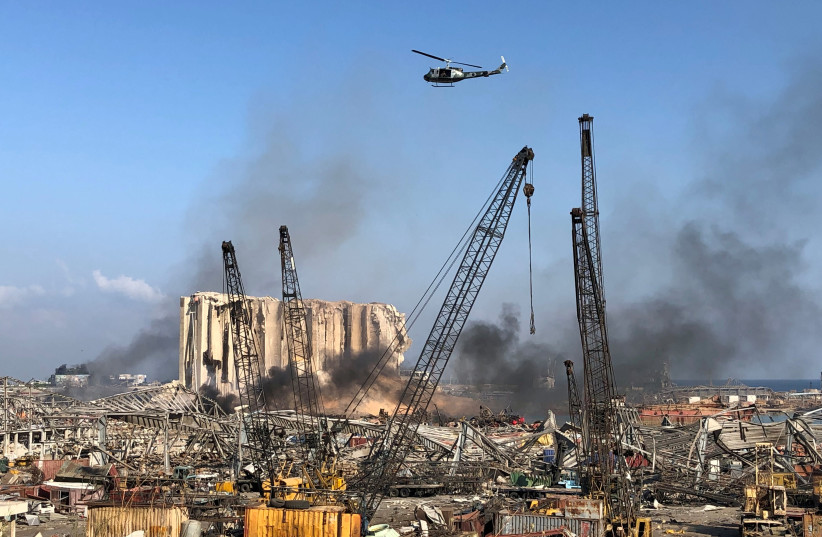 A Lebanese army helicopter flies over the site of Tuesday's blast in Beirut's port area (photo credit: REUTERS/ISSAM ABDALLAH)