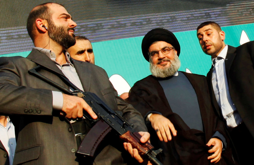 Lebanon's Hezbollah leader Sayyed Hassan Nasrallah, escorted by his bodyguards, greets his supporters at an anti-US protest in Beirut's southern suburbs, Lebanon September 17, 2012 (photo credit: REUTERS/SHARIF KARIM/FILE PHOTO)