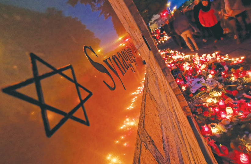 CANDLES LIGHT the scene of the fatal shooting outside a synagogue in Halle, Germany, in October 2019. (photo credit: REUTERS/HANNIBAL HANSCHKE)