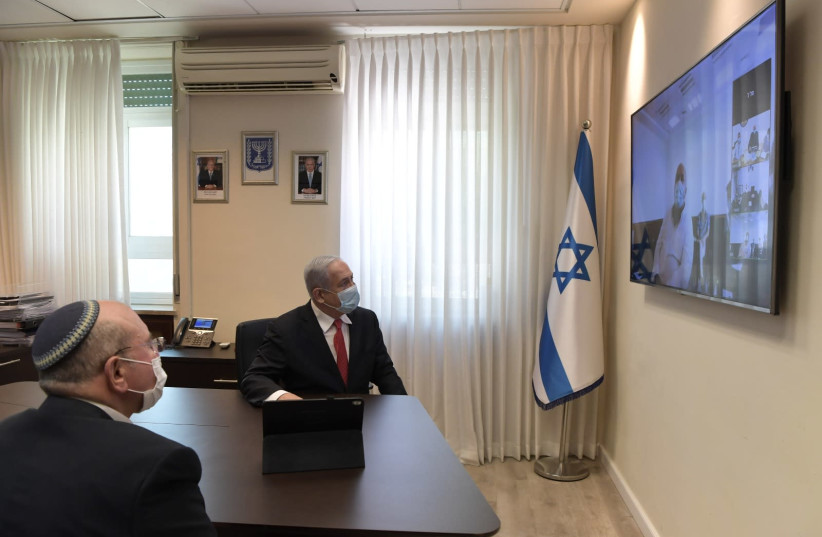 Prime Minister Benjamin Netanyahu holds a video call with IIBR members following the institute's progress toward launching a vaccine for the coronavirus. (photo credit: KOBI GIDEON/GPO)
